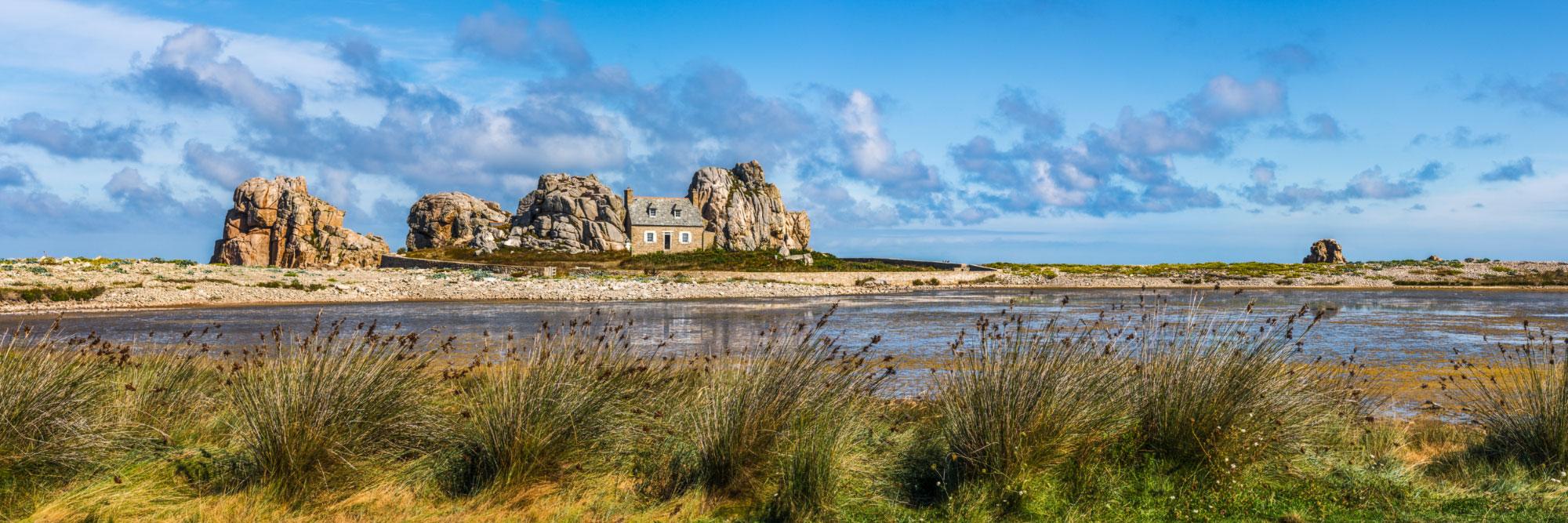 La côte de granit rose à Castel Meur, ajoncs devant des lagunes fermées par la recontre de deux tombolos, Plougrescant, Manche